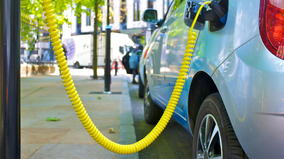A low angle view of an electric car connected to a spiral charging lead