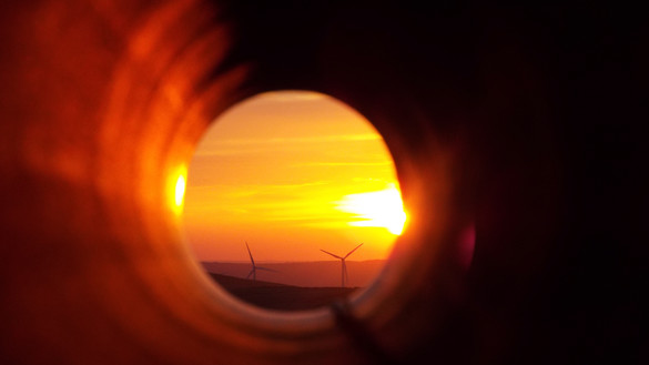 A view through a tunnel to show wind turbines at sunset