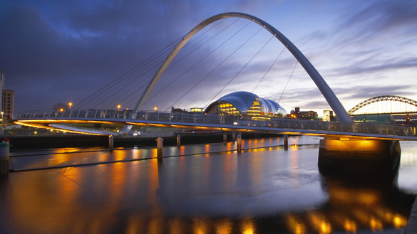 A twilight overview of a waterside bridge in Newcastle with lights reflecting on the water
